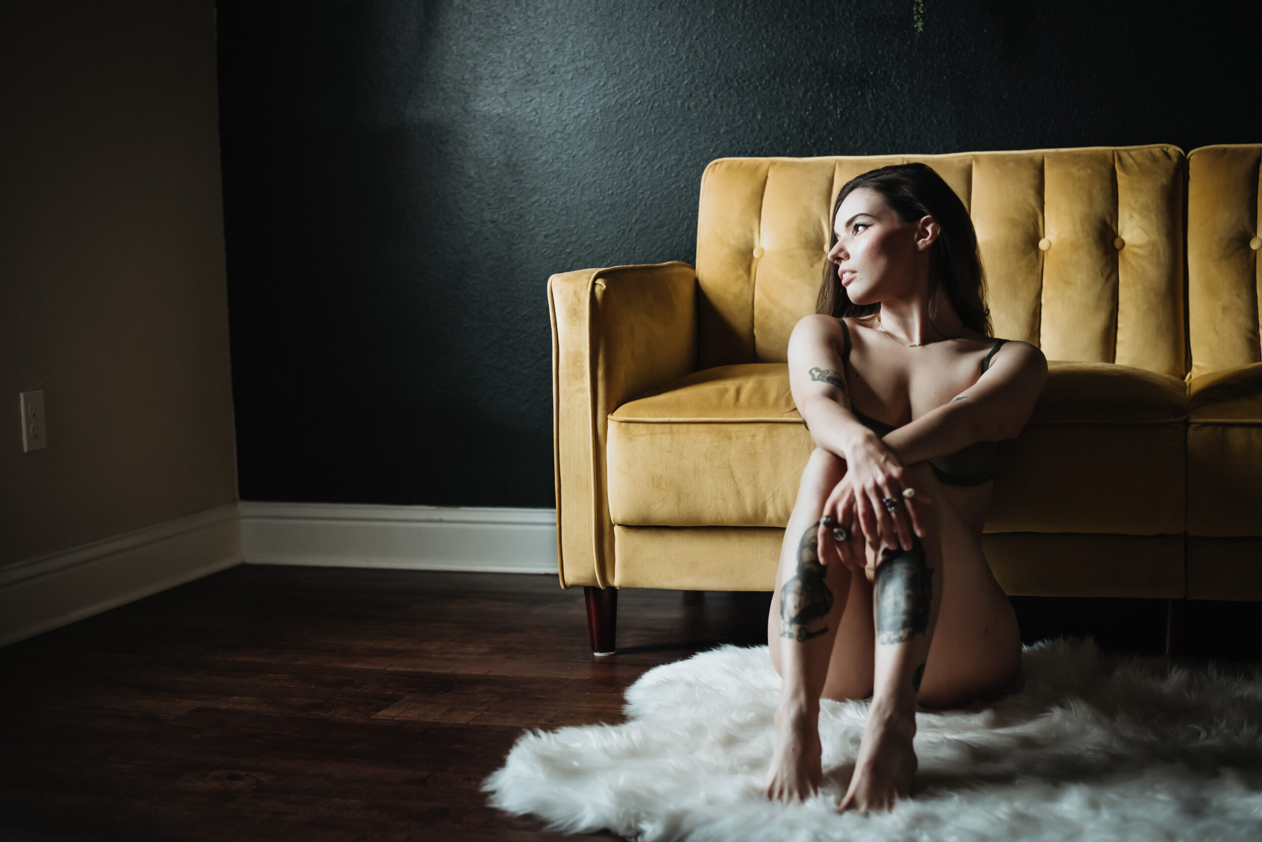 Boudoir photograph of a girl sitting on the floor with her wrists crossed on her knees next to a yellow sofa